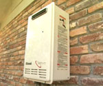 Tankless hot water heater mounted outside on brick wall of residence.